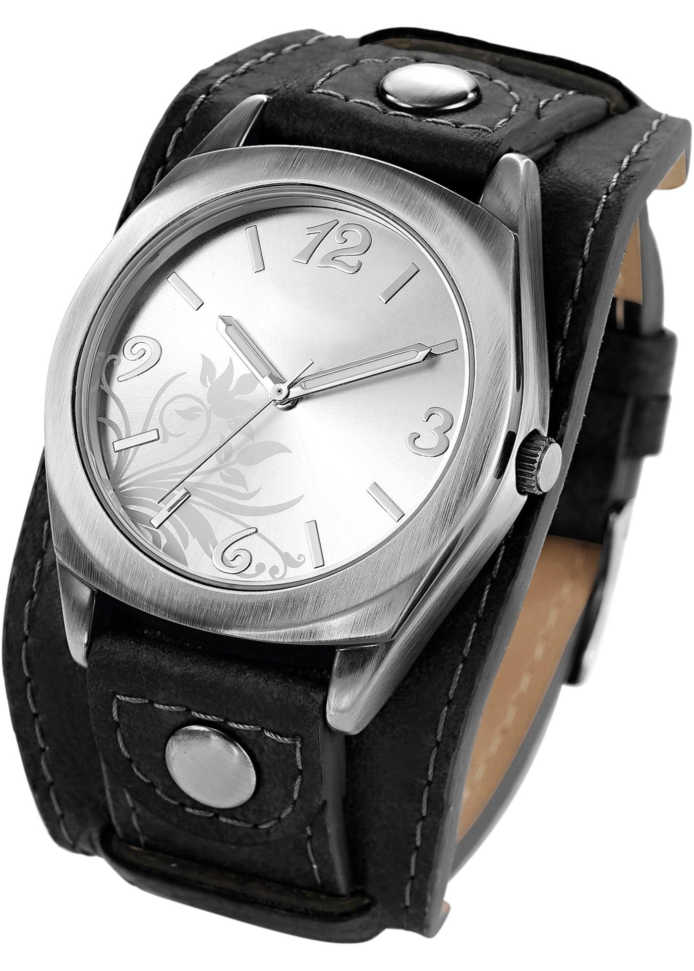 Véritable accessoire de mode, la montre Imke se compose d'un bracelet en matière synthétique imitation cuir et d'un cadran métallique féminin. Orné de fleurs et d'arabesques, le cadran est également doté de trois aiguilles. Idéale pour compléter une tenue