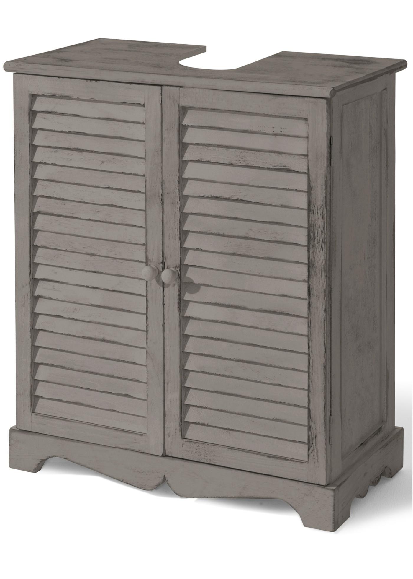 Meuble sous-lavabo avec portes à lamelles et socle sculpté. Aspect patiné. Livré monté.
